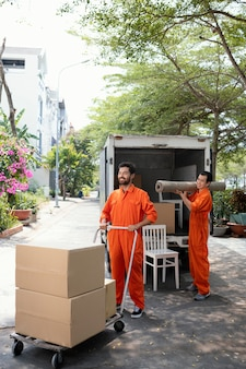 Vertical shot of young delivery men moving objects out of car