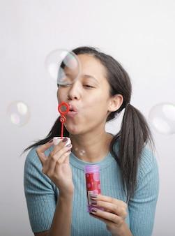 Colpo verticale di una giovane donna che soffia bolle di sapone