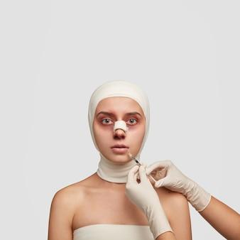Colpo verticale di giovane paziente femminile che subisce un intervento di chirurgia plastica del naso, ha bende mediche sulla testa