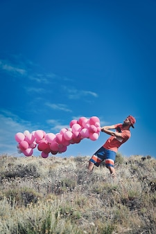 Colpo verticale di un giovane maschio che trasporta un mazzo di palloncini rosa su una superficie del cielo blu