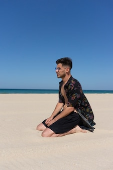 Vertical shot of a young male sitting on the sand at the beach