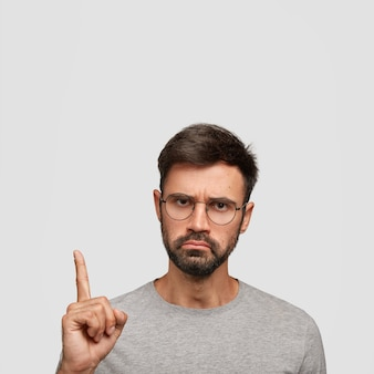 Vertical shot of young male with serious displeased expression, has thick stubble, dark hair, points with index finger upwards, dressed casually, isolated over white wall. look at this!