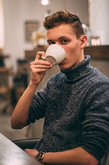 Colpo verticale di un giovane uomo che beve il caffè nella caffetteria