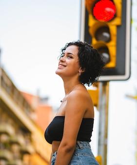 Colpo verticale di una giovane donna sorridente in strada