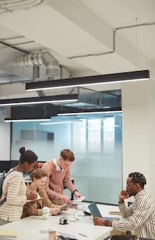 Вертикальный вид сбоку на разнообразную группу студентов, работающих вместе в современной школьной библиотеке и использующих компьютеры, скопируйте пространство