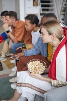 ポップコーンやおやつと自宅でスポーツの試合を見ている若者の多様なグループの垂直側面図