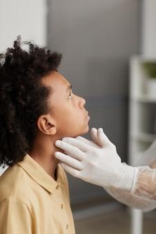 クリニックでの診察中にcovidのために男の子を調べている認識できない医師の垂直側面図のクローズアップ