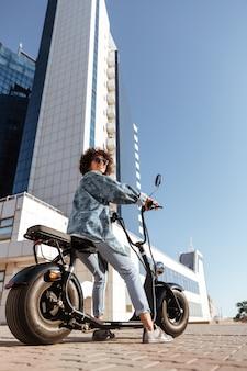 屋外の現代的なバイクの上に座って、よそ見サングラスで屈託のない巻き毛の女性の垂直方向の側面画像