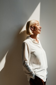 Vertical side view portrait of elegant mature woman lit by sunlight against white wall copy space