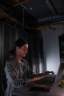 Vertical side view portrait of female network engineer using laptop while sitting in dark server room, copy space