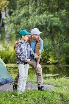 Vertical side view portrait of loving father teaching son fishing while enjoying camping trip together