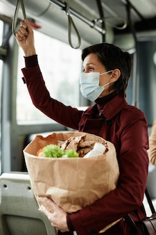 Вертикальный вид сбоку портрет взрослой женщины в маске в автобусе, путешествуя на общественном транспорте и держась за перила