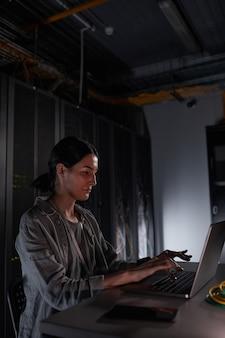 Вертикальный вид сбоку портрет женского сетевого инженера, использующего ноутбук, сидя в темной серверной комнате, копирование пространства