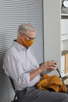 Вертикальный вид сбоку портрет современного пожилого человека в маске и использующего смартфон во время ожидания в очереди в медицинской клинике
