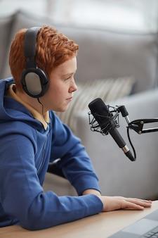ポッドキャストまたはオンラインストリームを録音しながらマイクに向かって話し、ヘッドフォンを着用している赤い髪の10代の少年の垂直側面図の肖像画