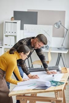 사무실에서 함께 작업하는 동안 청사진을 cdrawing 두 건축가의 세로 측면보기 초상화