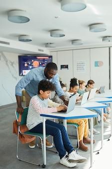 Вертикальный вид сбоку портрет мальчика, использующего компьютер в ит-классе с учителем-мужчиной, помогающим ему, копией пространства