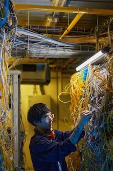 Вертикальный вид сбоку портрет молодого специалиста по сетям, соединяющего провода и кабели в серверной комнате, копией пространства