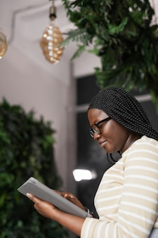 Vertical side view portrait of young african-american woman using digital tablet while standing in elegant office interior decorated by plants, copy space