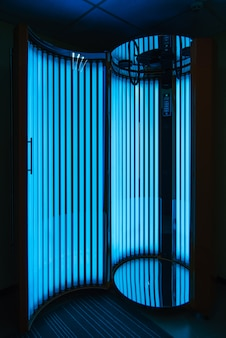 Vertical solarium with glowing blue light ultraviolet lamps