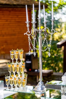 Vertical stand of champagne in the glasses. candelstick with pearl thread. nice tender decoration. celebration in summer.