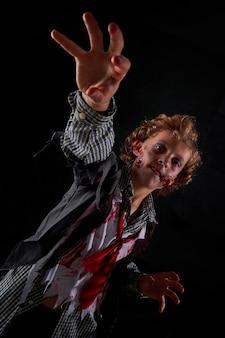 Вертикальное фото мальчика, замаскированного под зомби в крови, с поднятыми руками, пытающегося поймать что-то перед собой. хэллоуин