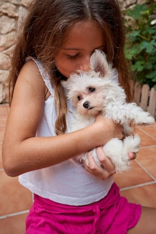 작은 흰색 강아지를 키스 하는 여자의 세로 재고 사진은 그녀의 팔에 개최. 애완 동물과 가족