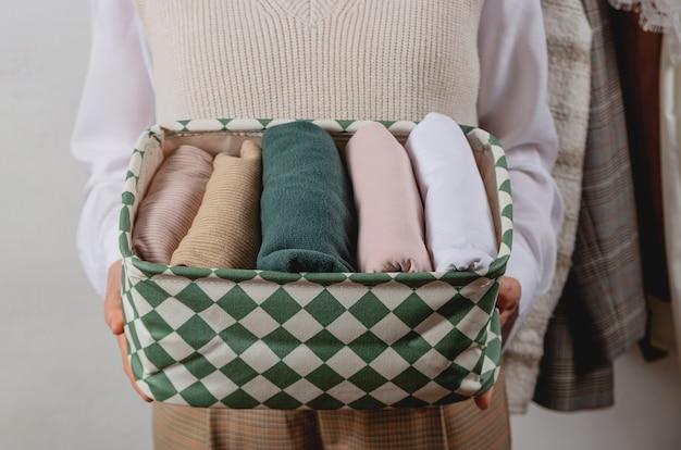 Вертикальное хранение одежды в контейнере в руках женщины