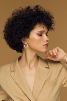 縦のスタジオ写真、ベージュの背景にファッショナブルなジャケットの巻き毛のブルネットの女の子。高品質の写真