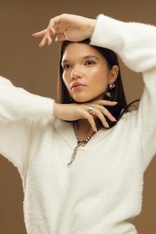 Вертикальное фото студии красивой модели брюнетки женской на бежевой предпосылке. фото высокого качества