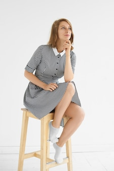 Vertical studio picture of beautiful young woman wearing elegant checkered dress with white collar sitting on high wooden chair, having dreamy thoughtful look, touching her chin and smiling
