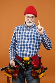 Vertical studio shot of serioues experienced unshaven mature plumber with belt kit of working tools strict look