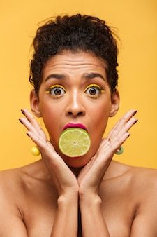 Vertical surprised afro american woman bulging eyes while putting half of fresh lime in mouth isolated, over yellow wall
