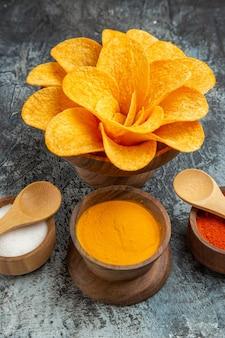 회색 테이블에 숟가락으로 꽃 모양의 다른 향신료처럼 장식 된 수직 맛있는 감자 칩