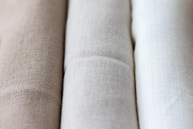 Вертикальный фактурный фон из трех видов натуральной льняной ткани, свернутой в свернутом виде. выборочный фокус. крупным планом вид
