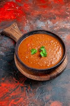 混合色の背景の右側にある茶色のまな板に垂直トマトスープ