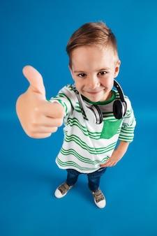 헤드폰으로 포즈를 취하는 어린 소년의 수직 평면도 이미지