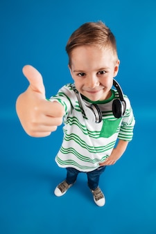 Vertical top view image of young boy posing with headphone