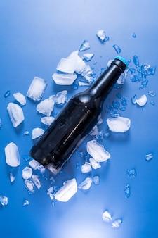 파란색 표면에 맥주 병 및 얼음의 수직 평면도