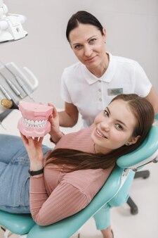 Вертикальный снимок красивой счастливой женщины и ее стоматолога, улыбающейся в камеру после стоматологического лечения, вид сверху