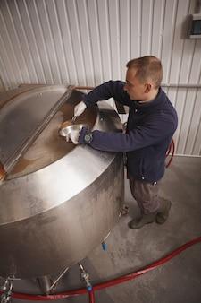 Вертикальный вид сверху работника пивоварни, проверяющего брожение пива в бочке