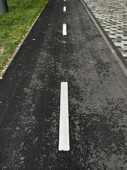 Вертикальный вид сверху мокрой велосипедной дорожки на открытом воздухе осенью