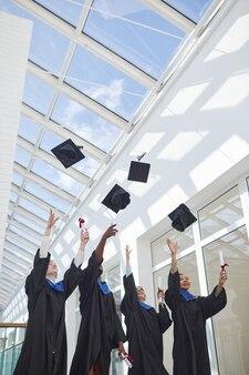 Вертикальный вид на разнообразную группу выпускников колледжа, бросающих шляпы в воздух против неба с солнечным светом, копирование пространства
