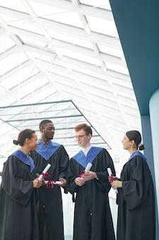 現代の大学のインテリアの屋内で卒業式のガウンを着て、元気にチャットしている若者の多様なグループの垂直方向のビュー