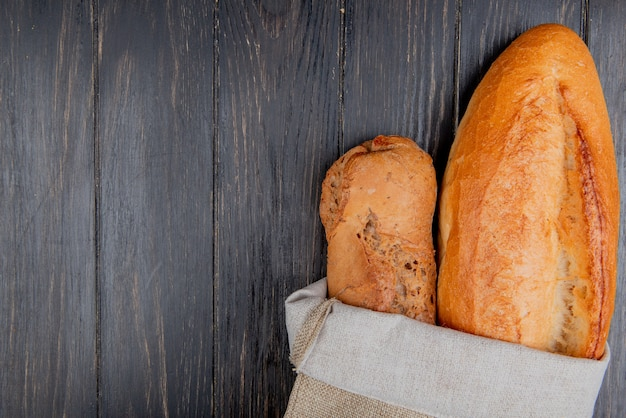 Vertical view of baguettes as black and vietnamese in sack on wooden background with copy space