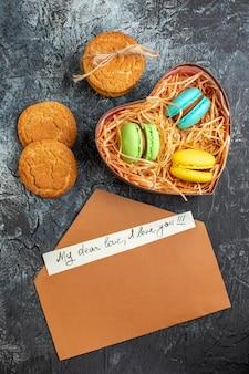 Vista verticale di una bellissima confezione regalo con busta di macarons e biscotti con lettera d'amore su sfondo scuro ghiacciato