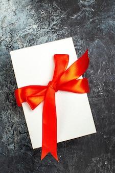 Vista verticale di scatole regalo splendidamente confezionate legate con nastro rosso su oscurità