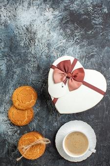 Vista verticale della migliore sorpresa con una bella confezione regalo e una tazza di biscotti al caffè per l'amato su sfondo scuro ghiacciato
