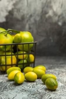 Vista verticale del cesto nero con mandarini verdi freschi e kumquat su sfondo grigio