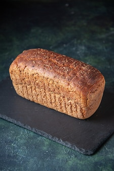 Vista verticale di pane nero su tavola nera su sfondo in difficoltà di colori misti